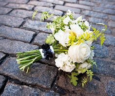 The bride carried a white bouquet of roses, hydrangeas and leaves to contrast her dark gown. See her black wedding dress here.
