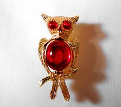 Owls rock! Cute textured goldtone owl brooch embellished with red cabochon eyes and body. Brooch measures 1 1/4 in width.  Please note that this a vintage,