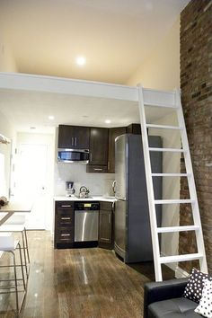 Sleeping loft and tiny kitchen. Looks and reminds me of a Japanese apartment