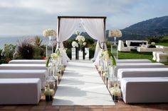 Shawna Yamamoto Event Design at Ritz Carlton, Laguna, outdoor ceremony, ocean mountain view, all white wedding, white guest seating benches, white curtains, framed alter, outdoor cocktail, clear flower pedestals