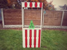 A carnival / fairground stall made pallets. These pallets were reclaimed and upcycled into a fun stall for kids to play with in the garden. Great for carnival themed kids parties.