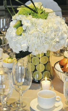 White floral centerpiece with halved limes for a touch of green. I like the idea of flowers and fruit in the centerpieces.
