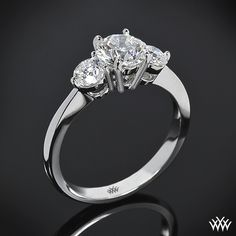 Delicate and refined, this gorgeous 'Trois Brilliant' 3 Stone Engagement Ring is guaranteed to delight. You can choose to purchase this ring as a setting only which will allow you to select all three diamonds or we can provide you with two A CUT ABOVE® Hearts and Arrows Diamond Melee side stones (0.50ctw; F/G VS) allowing you to find the perfect center dia...