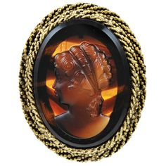 Circa 1950's  A regal brooch made of 14k gold and a large beautifully carved amber cameo.