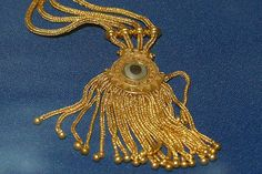 Assyrian Gold diadem from Nimrud 8th circa BC. A mesh diadem with tigereye agate, lapis lazuli, and a fringe of tiny gold pomegranates. The Iraq Museum - Baghdad