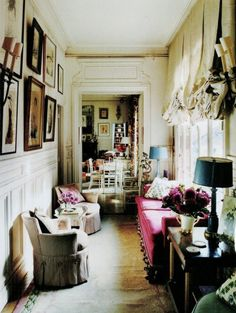 hallway-turned-narrow living room in Paris, rich beautiful curtains, fuschia couch, fresh flowers, lovely 1920s fashion illustrations