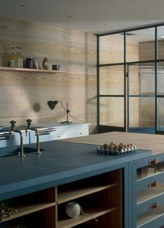 plain english. Open wood lower shelving. Glass front drawers. Integral wood cutting surface. Horizontal wood wall. Small guage steel and glass window wall.