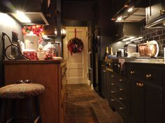 Benjamin Bradley: A view of the cozy kitchen with its black tile, pine cabinetry and antique terra cotta floor from Ann Sacks.