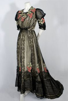Chantilly Lace Gown Having A Bodice With Full Pigeon-Breasted Front Typical Of The Period, Skirt Cut Longer And Fuller In Back Forming A Small Train, Colorful Floral Appliques And Black Velvet Bands Highlight Texture, Chantilly Lace Inserts, Rows Of Tucks      c.1905