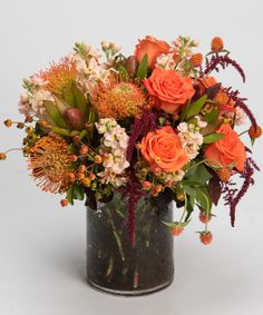 Harvest Moon This unique, gardeny style design of roses and pincushion protea with interesting accents of peaches, burgundies, and greens is arranged in our clear glass cylinder vase.