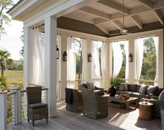 Stunning covered deck with black lanterns flanked by billowing white outdoor drapes
