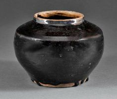 A Chinese Black Glazed Stoneware Jar, probably Qing Dynasty (1644-1911) or earlier, ovoid body with tapering shoulders and short neck, overall mottled black glaze pooling above the unglazed base, height 5 1/4 in., diameter 7 1/4 in
