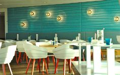 White chairs with red orange legs, turquoise walls. Restaurant.