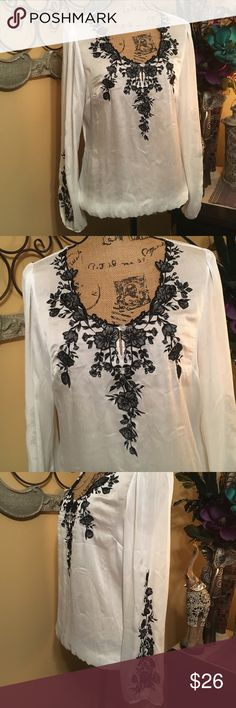 "White House Black Market Tunic Sheer white polyester tunic with black floral embroidered accents. Detailed embroidered neckline with black stitching & mesh backgrounds. One opaque front button closure. Wide belled sleeves with elastic end trim & floral embroidery down the sides. Elastic bottom trim & back floral embroidery. Fabric is translucent & without lining. Sz 8. Like new. 38""-40"" very loose fitting bust, 23"" length & 25"" sleeves. White House Black Market Tops Tunics"