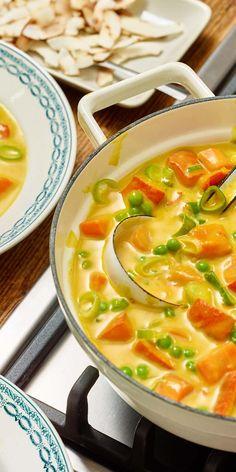 Lust auf Curry? Dann probier diese vegane Variante mit Kürbis, Erbsen und Kokosmilch. Garniert mit gerösteten Kokoschips, einfach köstlich!