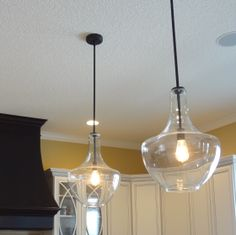 Graceful glass and #Edison #bulbs in these large #pendants hung above a kitchen #island.   |   VillageHomeStores.com
