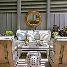 Neutral gray walls help keep this outdoor space cool, along with a light striped fabric. Railroading the stripes (running them horizontally) creates a bolder effect. coastalliving.com