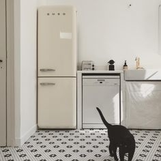 """The """"back kitchen,"""" with a newly laid black and white tile floor and cream-colored Smeg fridge. Notice the simple, flat sink skirt. Smeg Kitchen, Smeg Fridge, Best Flooring For Kitchen, White Appliances, Black And White Tiles, French Lessons, Rustic Kitchen, Kitchen Ideas, Kitchen Design"""
