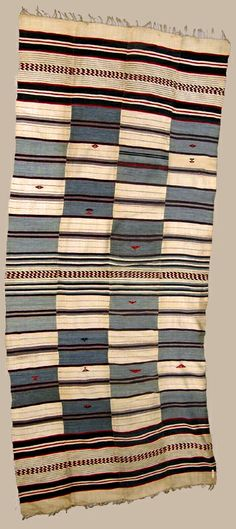 Africa | Kpokpo cloth from the Mende; Sherbro people of Sierra Leone | Cotton; composed of four wide strips, measuring 305mm in width, decorated in bands of cream, and indigo-dyed, cotton, and red thread. Sewn together they create a chequered design, bordered by bands of zigzags of red and blue. | ca. prior to 1934.
