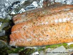 """Tinfoil Baked Salmon with Asparagus  2, 6 oz. salmon fillets 1 bunch asparagus, woody ends trimmed 1/2 C. sliced onion 2 T. butter my house seasoning (equal parts garlic powder, onion powder and pepper...combine and store in an airtight container) lemon juice dried dill weed tinfoil  Tear off two pieces of tinfoil about 10"""" long.  Place half of the asparagus in the center of each piece of tinfoil.  Top with half of the onions in each and then put 1 T. of butter on the top of the onions…"""
