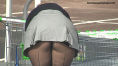 Candid public pantyhose upskirt woman in short skirt and black seamed pantyhose tights outdoors.