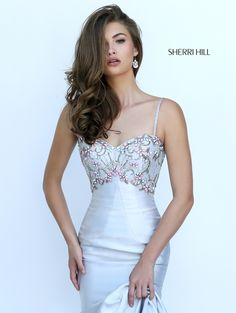 Slinky satin cleaves sensually to the figure in the Sherri Hill 50284 trumpet silhouette prom dress. The bodice showcases a sweetheart neckline and is embellished with beading, creating an inverted empire waistline. Delicately beaded spaghetti straps span the shoulders to meet the tapered bandeau back strap which frames a diamond midriff cutout. The trumpet skirt flares smoothly and showcases a glamorous inset sweep train.