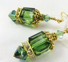 Green Irish and Gold Flower Swarovski 10mm Cube Earrings    Bring a little luck to your love life with these Green Irish and Gold Flower Swarovski 10mm Cube Earrings Gold beadcaps withflowers add beauty and charm to these huge 10mm Swarovski Peridot Satin cubes, offset on the bottom with 8mm gold electroplated crystal spacers and rare 8mm Swarovski Tourmaline AB bicones. They are topped with delicate antique gold spacer beads and Swarovski Peridot Satin 4mm bicones and put on 14k gold fill…