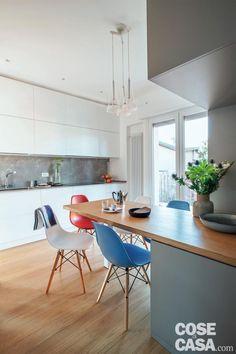 cucina, composizione a parete in laccato bianco, alzata grigia, portafinestra, bancone a penisola, sedie di design colorate, lampade a sospensione, pavimento in parquet di rovere