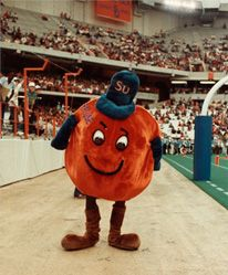 "Following the sidelining of the Saltine Warrior and the briefly adopted Roman Gladiator character, an Orange ""with appeal"" was introduced in 1980 (Daily Orange, April 4, 1980). Eric Heath, an SU cheerleader, is credited with designing and crafting the first costume for the rotund and fuzzy Orange. The mascot was known as ""The Orange"" until 1990, when the name Otto first came into use. (Courtesy of archives.syr.edu)"