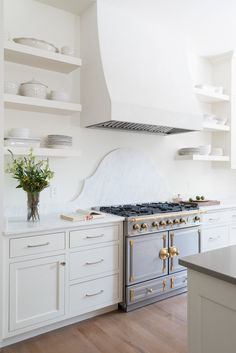 Brushed light colored hardware on white cabinets