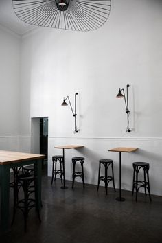 Tall stool seating against wall, with individual lights.   Bar-Co-Helsinki
