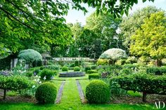 An heirloom stone basin centers a walled garden, where topiaries add rhythm and whimsy.