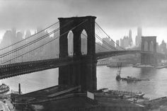 Storm clouds hover over the Brooklyn Bridge and the ghostly skyscrapers of Manhattan's financial district in March 1946.