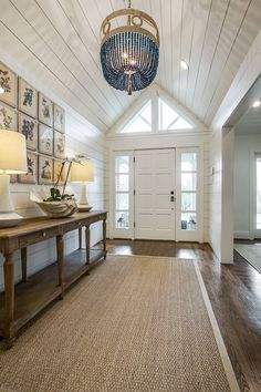 coastal inspired foyer/hallway with shiplap, planked ceilings/walls, sisal indoor/outdoor rug