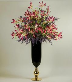 Luxurious opulent flower arrangement consists of resh touch pink gloriosa and purple limonium set in a tall black and gold goblet vase. An exclusive Demmery's exclusive creation. Artificial Flower Arrangements, Artificial Silk Flowers, Floral Arrangements, Champagne Cooler, Spider Plants, Taking Shape, White Orchids, Lush Green, Faux Flowers