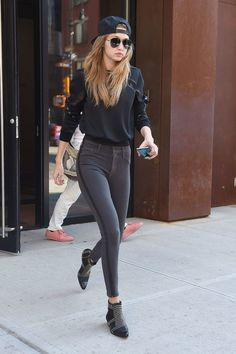 Gigi Hadid wears gray jeans, a sweatshirt, and studded boots, emanating edgy street style vibes.