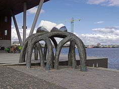 https://flic.kr/p/MVTYD3   2016.10 - Amsterdam photo of urban sculpture art - A bronze sculpture touches the sky on the border of the waterfront IJ - geotagged free urban picture, in public domain / Commons CCO; Dutch urban photography by Fons Heijnsbroek, The Netherlands   Amsterdam photo of urban outdoor public art. Picture of a large bowed bronze sculpture, touching the cloudy blue sky, on the border of the waterfront IJ. Location is on the corner of the street Van Diemenstraat and the…