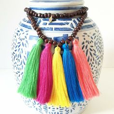 Dark brown wood beads accented with five bright summer-toned bohemian tassels.
