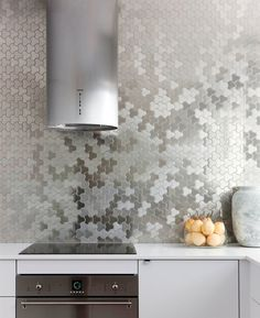 Kitchen Design Idea - Install A Stainless Steel Backsplash For A Sleek Look   Stainless steel tiles cover the back wall of this modern kitchen to create a unique look that's easy to clean.
