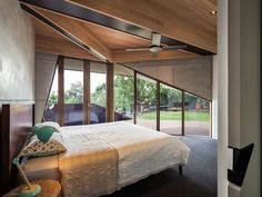 Master bedroom with articulated ceiling beams discretly shielded externally by the chamfered compressed cellulose reinforced sheet and spotted gum timber balcony | Chamfer House by Mihaly Slocombe (2015) | Frankston South, Victoria, Australia | photo: Andrew Latreille
