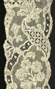 Mechlin  Here we see another exquisite lappet made in Flanders in the first half of the 18th century. This complex example was made with fine threads equal to those in the piece above, creating lovely transparencies. The motifs were outlined with a heavier thread, and a distinctive mesh ground was used. The design is composed of floral motifs along with scrolls and cartouches enclosing small trefoils