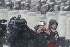 Reporters work during clashes between protesters and police in Kiev, Ukraine, on Wednesday. (AP Photo/Efrem Lukatsky)