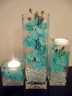 teal flowers with silver beads or pearls in a clear vase.