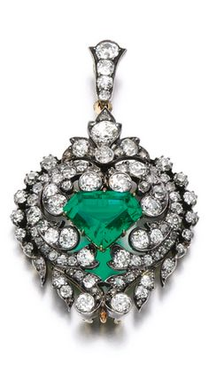 Emerald and diamond brooch/ pendant, late 19th century Of foliate and scroll design, set with a trapeze-shaped emerald, circular-cut and rose diamonds, detachable brooch and pendant fittings.