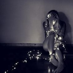 woman wrapped in christmas tree lights