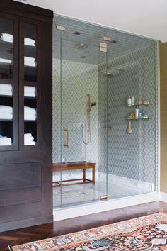 Bathroom - Walk in glass shower with bench plus a dark espresso linen cabinet.