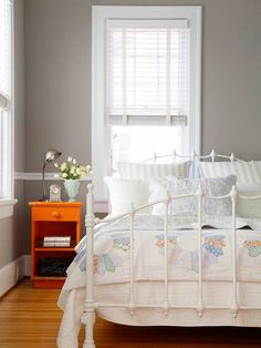 Vintage Color Scheme~ In this bedroom, a contemporary paint palette of warm gray on the walls and an orange painted nightstand make the flea market furnishings shine. An old white metal bed is dressed in new vintage-look linens layered with an antique quilt made in a multi-color Dresden plate pattern. The cocooning color scheme wraps up style and function in a pretty package.