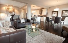 Carleton in EvansRidge - main floor with cream walls, trendy rich grain hardwood and dark brown leather sofas