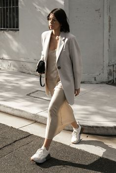 15 Trending Fall Styles To Get Inspired: Fashion blogger 'Modern Legacy' wearing an ivory blazer, a cream slip dress, white chunky sneakers and a black bag. fashion 2018, street style, fall outfit, fall fashion trends, fall trends 2018, casual outfit, comfy outfit, neutral outfit, minimal outfit, dad sneakers, #fashion2018, #fallstyle #streetstyle #casualstyle #dadsneakers #slipdress #blazer #neutrals #minimal