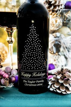 """Our all time bestseller. And perhaps the perfect wine lover's Christmas gift. Personalized, elegant, and completely beautiful, this etched bottle design features our """"starry"""" Christmas tree built with shimmering silver stars to give it that glittery, wintry feel. Atop the tree sits a single gold star; golden """"Happy Holidays"""" text is placed below. Personalization is included at the bottom of the entire design."""